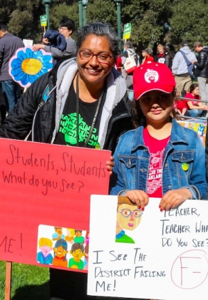 Oakland teacher Anita Gutierrez at a strike rally with her daughter, a second grader.
