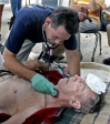 A doctor tends to a man hurt by Hurricane Katrina.