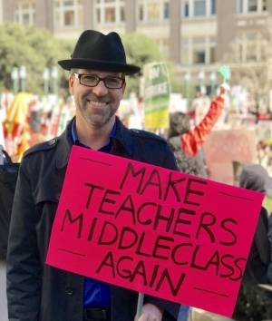 The author at a strike rally, with the sign that would be destroyed by rain the next morning on a picket line.