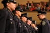 Assistant Chief of Police Paul Figueroa, center, congratulates graduates after they are presented with their badges during the graduation ceremony for the 167th Police Academy at the Scottish Rite Temple in Oakland, California