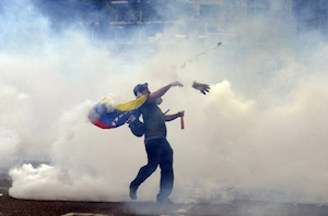 A demonstrator throws stones at riot police during an anti-government protest in eastern Caracas, Venezuela, on February 27th, 2014.