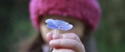 kid giving flower
