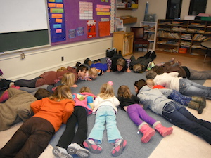 "Students in the Kindness Curriculum work on ""mindful movement,� getting ready for cobra pose."
