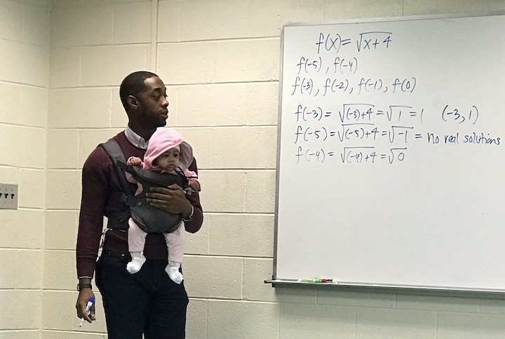 professor holds baby