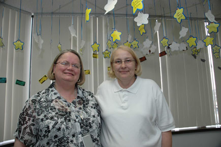 In the Michigan hospital department where Sarah Boik (left) and Deb LeJeune work, staff members hang a star with each co-worker's name on it every time someone does something exceptional. Their office has been studied as an example of a compassionate workplace.