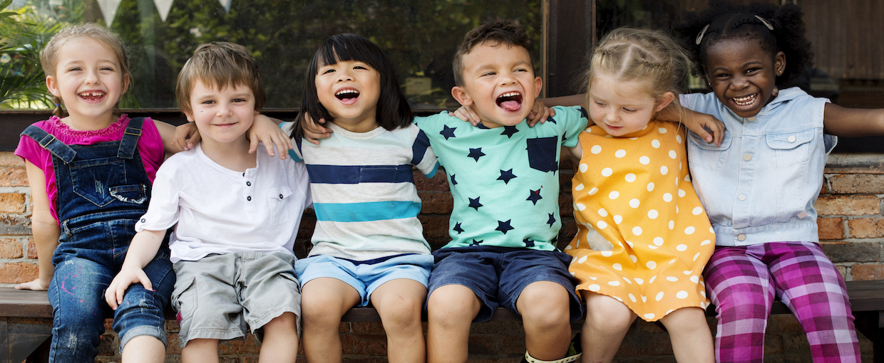 Diverse children laughing on a bench